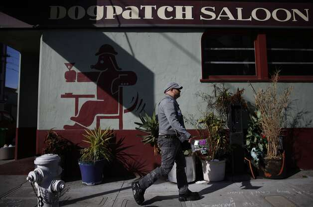 James Ellis of San Francisco walks past the Dogpatch Saloon on his way to work in the budding neighborhood. Photo: Lea Suzuki, The Chronicle