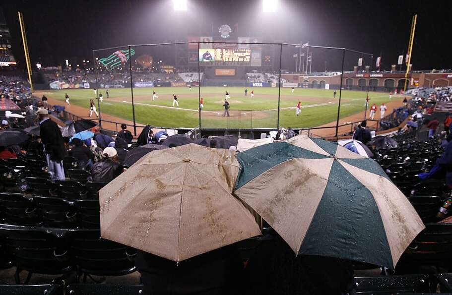 Come rain or come shine, fans watch the Giants play the Angels in March 2006.