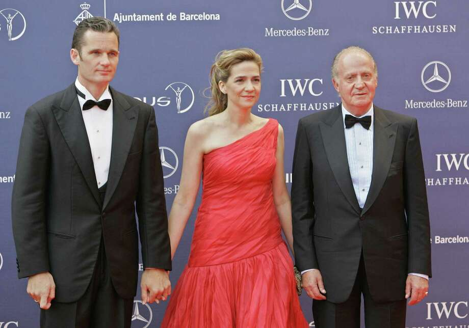 FILE - In this May 22, 2006 file photo, Spain's King Juan Carlos arrives with his daughter, Princess Cristina, and her husband, Inaki Urdangarin, for the Laureus World Sports Awards in Barcelona, Spain. Urdangarin is accused of having used his position to embezzle several million dollars in public contracts assigned to a nonprofit foundation he set up. The corruption scandal is contributing to the public's diminishing respect for the monarchy. With the 75-year-old king's reputation in decline and several health scares recently, Juan Carlos and the Spanish monarchy are facing one of their biggest crises ever. The last time Juan Carlos appeared in public in front of thousands of people, he was greeted by persistent heckling and whistling never before seen during his reign of nearly four decades. (AP Photo/Jasper Juinen, File) Photo: Jasper Juinen, STF / AP
