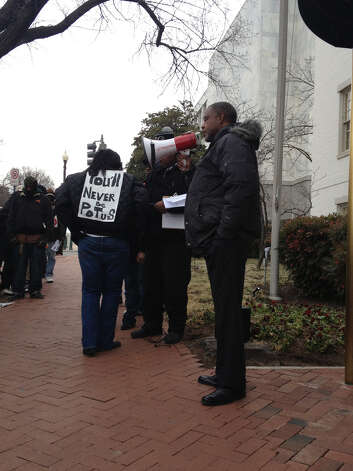 Rev. James Caldwell leads protesters for expanded Medicaid outside the Republican National Club in Washington where Gov. Rick Perry spoke to Texas Society members.