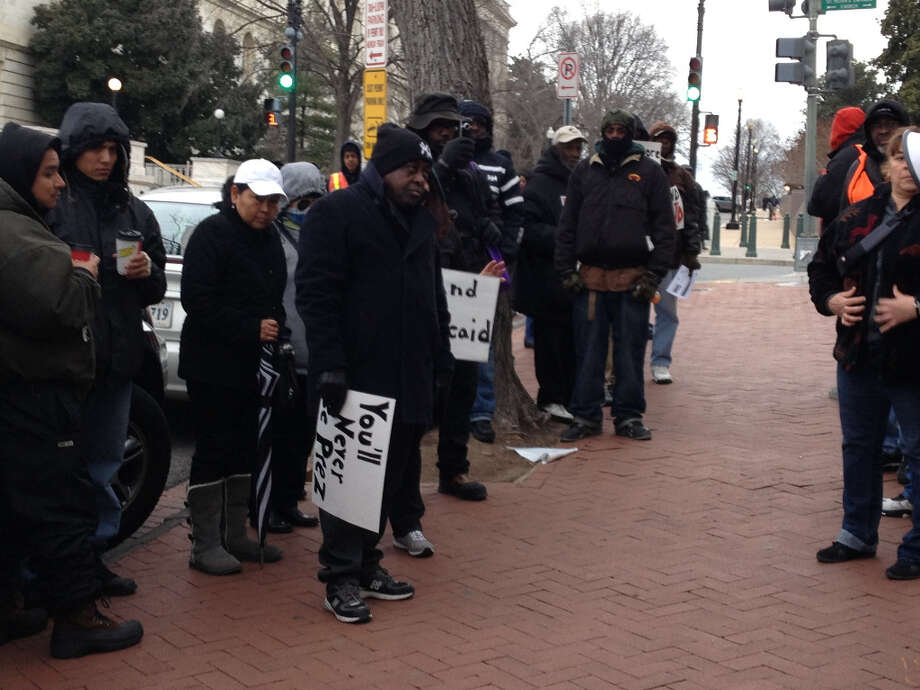 Protesters from the 'Texas Organizing Project' and 'Perry No Care' stood outside the Republican National Club on Capitol Hill to protest Gov. Rick Perry's decision to not expand Medicaid. February 22, 2013.