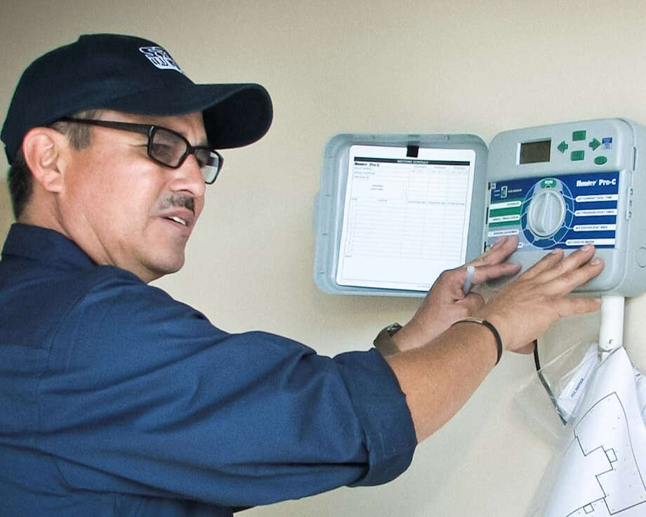 SAWS consultant Marty Garcia adjusts the timer on an automatic irrigation system. Photo: Courtesy San Antonio Water System