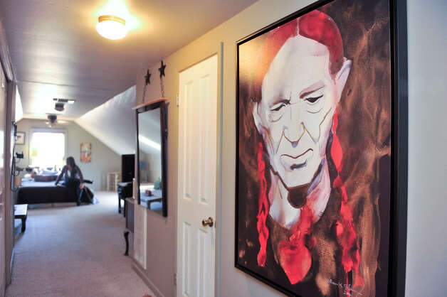 A portrait of Willie Nelson by artist Bill Stid-ham hangs in the hallway to the master suite.