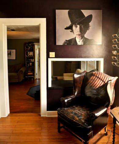 A painting of Mick Jagger along with a leather wingback chair are part of the kitchen.