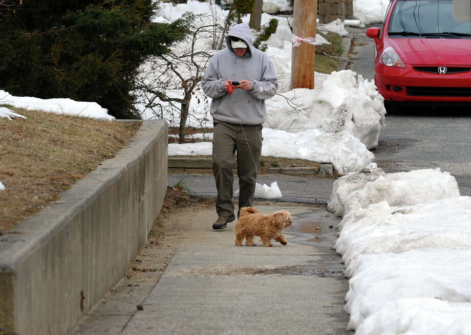 James Trembicki checks messages on his smart phone as he walks his dog Sasha after work along Matthew Street in Milford, Conn. on Friday February 22, 2013. Photo: Christian Abraham / Connecticut Post