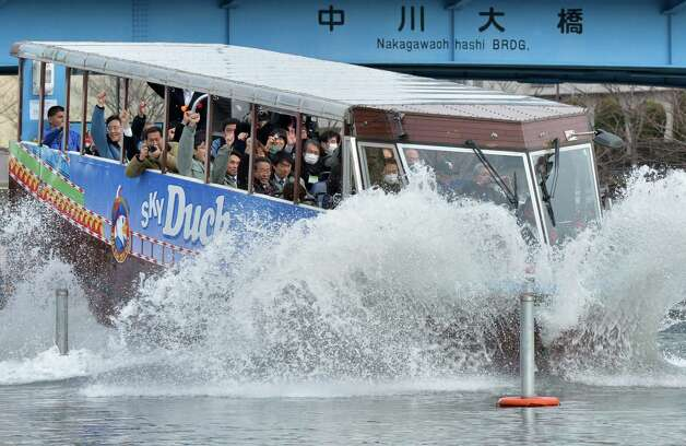 "An amphibious bus ""SKY Duck"" goes into the water during its trial run in Tokyo on February 22, 2013. Japan's Hinomaru bus service company will begin a sightseeing service with two amphibious buses from March 17 for the first time in Tokyo.    AFP PHOTO / KAZUHIRO NOGI Photo: KAZUHIRO NOGI, Getty / 2013 AFP"