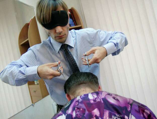 Oleg Maksyuk, a Ukrainian hair-stylist wearing a mask while using two pairs of scissors, cuts the hair of a client in a salon in the Ukrainian  Black Sea city of Sevastopol, on February 18, 2013. The hair-stylist mastered the unusual work style to attract more clients to his salon. AFP PHOTO/ Vasiliy BATANOV Photo: AFP, Getty / 2013 AFP