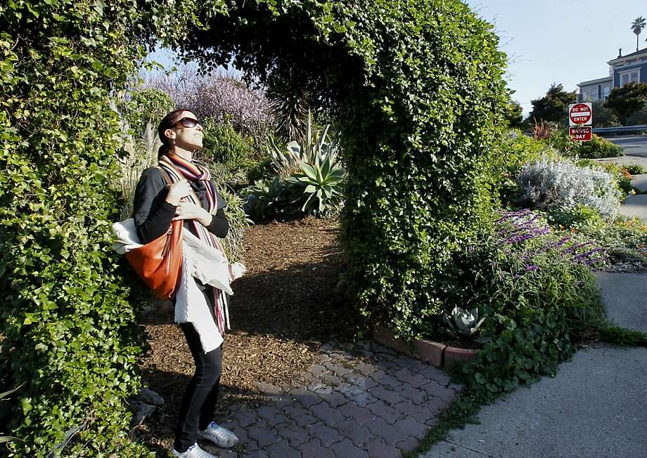 Annie Shaw emerges from the garden she instigated on a former trash-strewn vacant spot on Pennsylvania Avenue. Photo: Brant Ward, The Chronicle
