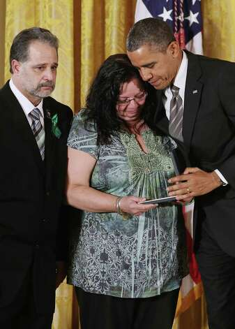 "U.S. President Barack Obama presents Donna and Carlos Soto Sr. with the 2012 Presidential Citizens Medal, the nation's second-highest civilian honor, on behalf of their daughter Victoria Soto in the East Room of the White House February 15, 2013 in Washington, DC. First grad teacher, Victoria Soto was killed during a mass shooting that left 26 people dead at Sandy Hook Elementary School in December 2012. ""Their selflessness and courage inspire us all to look for opportunities to better serve our communities and our country,"" Obama said about this year's recepients. Photo: Chip Somodevilla, Photo By Chip Somodevilla/Getty / 2013 Getty Images"