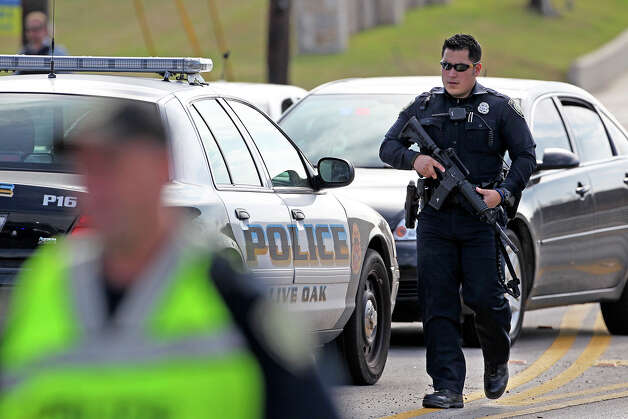 An officer carries his service rifle along Kitty Hawk Road outside of the Summit Ridge subdivision as officers converge on the site where a suspect was spotted in the shooting of a deputy. Photo: TOM REEL