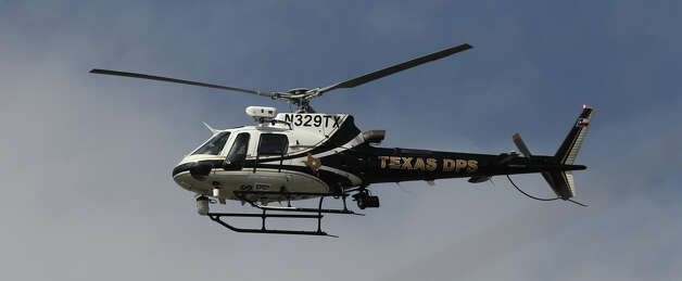 A Department of Public Safety helicopter flies Friday February 22, 2013 over a scene in Converse involving the shooting of a Bexar County deputy. The suspect in the shooting was killed. Photo: JOHN DAVENPORT, San Antonio Express-News / ©San Antonio Express-News/Photo Can Be Sold to the Public