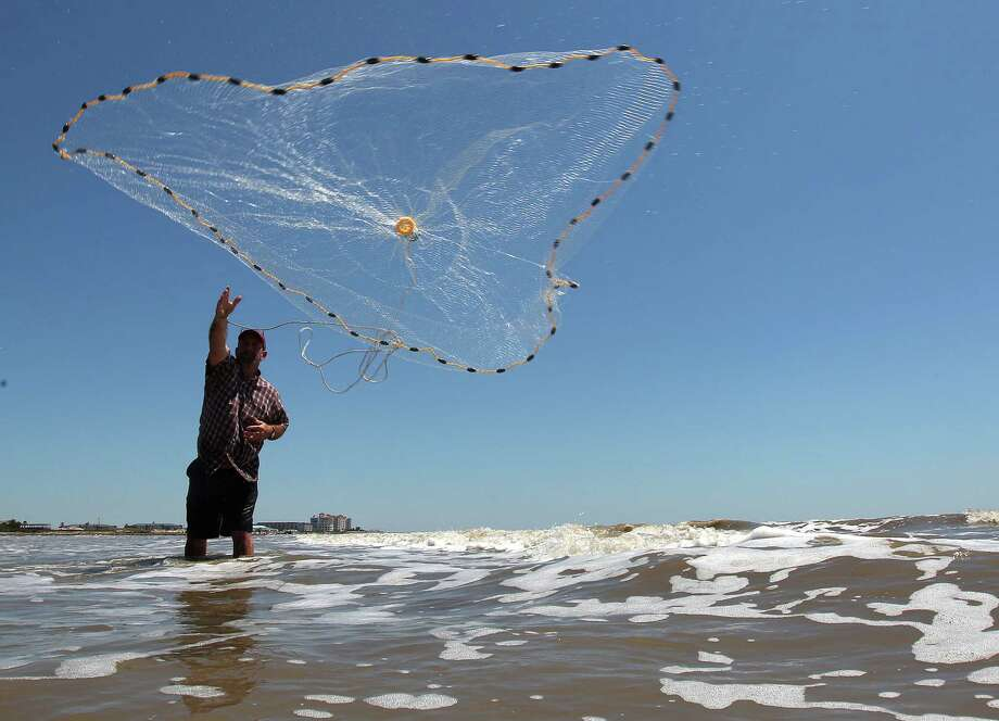 An avid fisherman casts his net for fish on Galveston's sunnny beach. Photo: Johnny Hanson, Staff / © 2012  Houston Chronicle