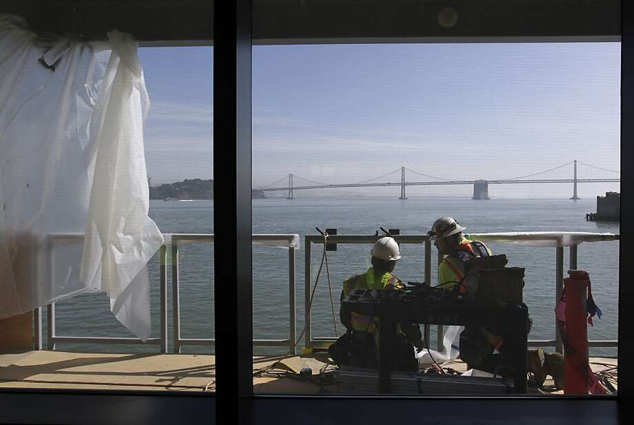 Construction workers attach panels to a railing on the second floor of the new cruise ship terminal at Pier 27 in San Francisco. Photo: Paul Chinn, The Chronicle