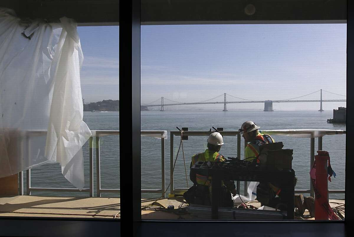 Construction workers attach panels to a railing on the second floor of the new cruise ship terminal at Pier 27 in San Francisco, Calif. on Friday, Feb. 22, 2013. They are seen through fritted glass, which was installed to deter birds from striking the panes and which also has thermal properties.