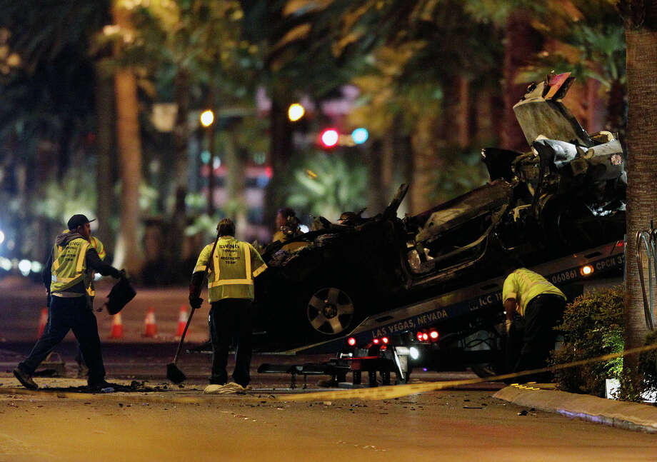 Tow truck drivers clean up and tow away cars involved in a drive-by shooting on Las Vegas Boulevard in Las Vegas Thursday, Feb. 21, 2013.  (AP Photo/Las Vegas Review-Journal, John Locher) LOCAL TV OUT; LOCAL INTERNET OUT; LAS VEGAS SUN OUT Photo: John Locher, MBO / Las Vegas Review-Journal