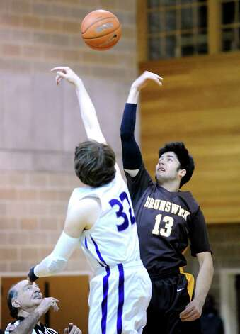 At right, Nick Kono # 13 of Brunswick jumps center against Mike Jurr # 32 of Masters during the FAA boys high school basketball semifinal between Brunswick School and Masters at Brunswick in Greenwich, Friday night, Feb. 22, 2013. Photo: Bob Luckey / Greenwich Time