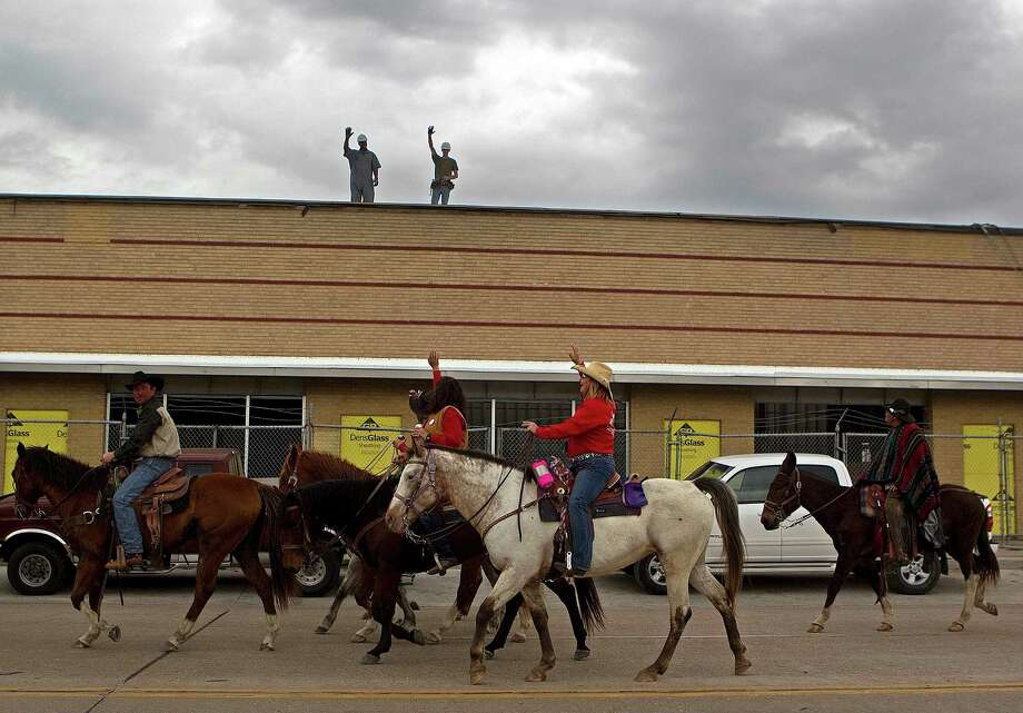 Construction workers wave as the Texas Independence Trail Ride group makes its way along the 200 block of West Gray Street on their way to Memorial Park to kick off the Houston Livestock Show and Rodeo Friday, Feb. 22, 2013, in Houston. Photo: Johnny Hanson, Houston Chronicle / © 2013  Houston Chronicle