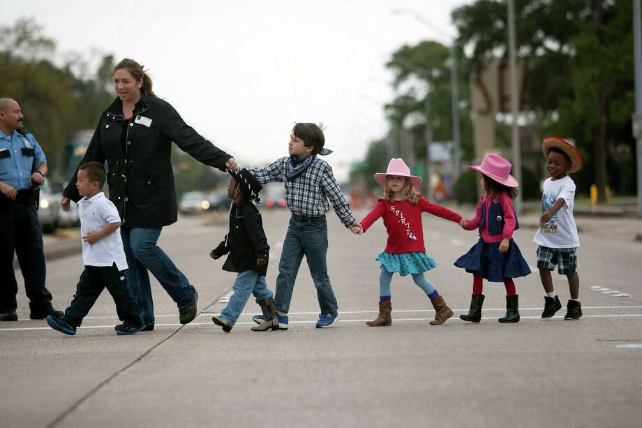 Wearing their western wear, a group of Garden Oaks Elementary School students make their way back to school after visiting The Spanish Trail Ride group in a parking lot on Shepherd near 43rd to Memorial Park to kick off the Houston Livestock Show and Rodeo Friday, Feb. 22, 2013, in Houston. Photo: Johnny Hanson, Houston Chronicle / © 2013  Houston Chronicle