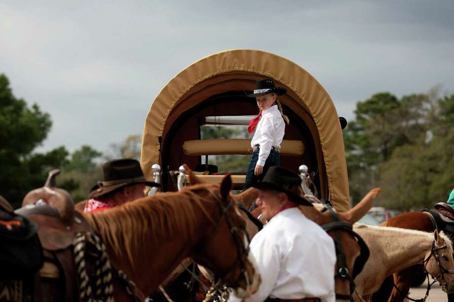 Mikenzy Whitmire, 6, from Cleveland, sits on her covered wagon as The Spanish Trail Ride group prepared to make their way from a parking lot on Shepherd near 43rd to Memorial Park to kick off the Houston Livestock Show and Rodeo Friday, Feb. 22, 2013, in Houston. Photo: Johnny Hanson, Houston Chronicle / © 2013  Houston Chronicle