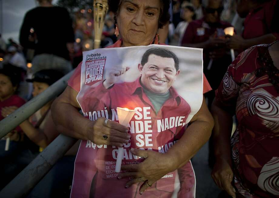 "A woman holds a candle along with a poster of Venezuela's President Hugo Chavez at a candlelight vigil to pray for his health as he remains in a hospital undergoing cancer treatment, in Caracas, Venezuela, Friday, Feb. 22, 2013. The Venezuelan government provided an update on Chavez's condition Thursday night, saying that he remained at a military hospital in Caracas and that ""the medical treatment for the fundamental illness continues without presenting significant adverse effects."" (AP Photo/Ariana Cubillos) Photo: Ariana Cubillos, Associated Press"