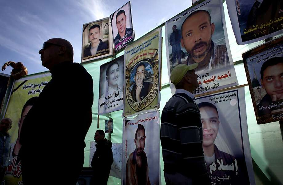 "Egyptian men inspect posters of slain men with their picture and Arabic that reads their names ""Ahmed el-Syyed, Mohammed Ali Ibrahim, Islam, Osama el-Sherbiny, Ahmed el-Shahat,"" at a protest camp in front of the provincial government headquarters, unseen, during the fifth day of a general strike, in Port Said, Egypt, Thursday, Feb. 21, 2013. (AP Photo/Nasser Nasser) Photo: Nasser Nasser, Associated Press"