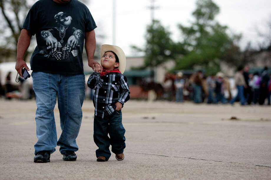 Thomas Fuentes, 3, walks with his uncle, Juan Cazeno after the two visited The Spanish Trail Ride group in a parking lot on Shepherd near 43rd to Memorial Park to kick off the Houston Livestock Show and Rodeo Friday, Feb. 22, 2013, in Houston. Photo: Johnny Hanson, Houston Chronicle / © 2013  Houston Chronicle