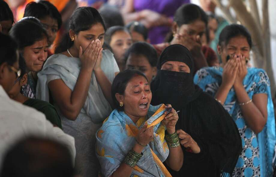 Relatives and neighbors mourn by the body of Swapna Reddy, killed in Thursday's explosion, at their house in Hyderabad, India, Friday, Feb. 22, 2013. A day after two bicycle bombs killed more than a dozen people and wounded more than 100, investigators into India's worst bombing in more than a year searched Friday for possible links to anger over the execution of a Muslim militant. (AP Photo/ Mahesh Kumar A.) Photo: Mahesh Kumar A, Associated Press