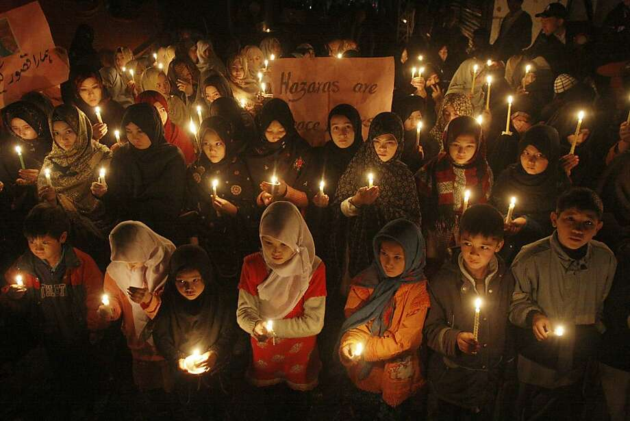 Pakistani children hold candles at the site of Saturday's bombing, in Quetta, Pakistan, Thursday, Feb. 21, 2013. Pakistani Shiites buried their kin killed in a massive bombing last weekend in the southwestern city of Quetta but the funeral on Wednesday was marred by gunfire as both protesters and police fired into the air. (AP Photo/Arshad Butt) Photo: Arshad Butt, Associated Press