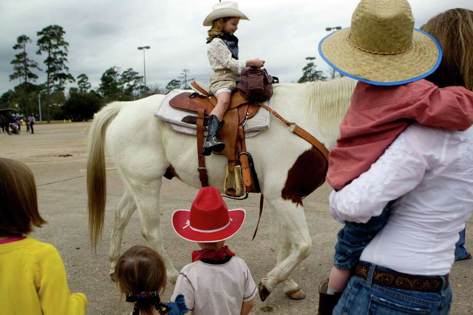 Juliet Wagner, 6, is treated to a horse ride while visiting with The Spanish Trail Ride group before they made their way from a parking lot on Shepherd near 43rd to Memorial Park to kick off the Houston Livestock Show and Rodeo Friday, Feb. 22, 2013, in Houston. Photo: Johnny Hanson, Houston Chronicle / © 2013  Houston Chronicle