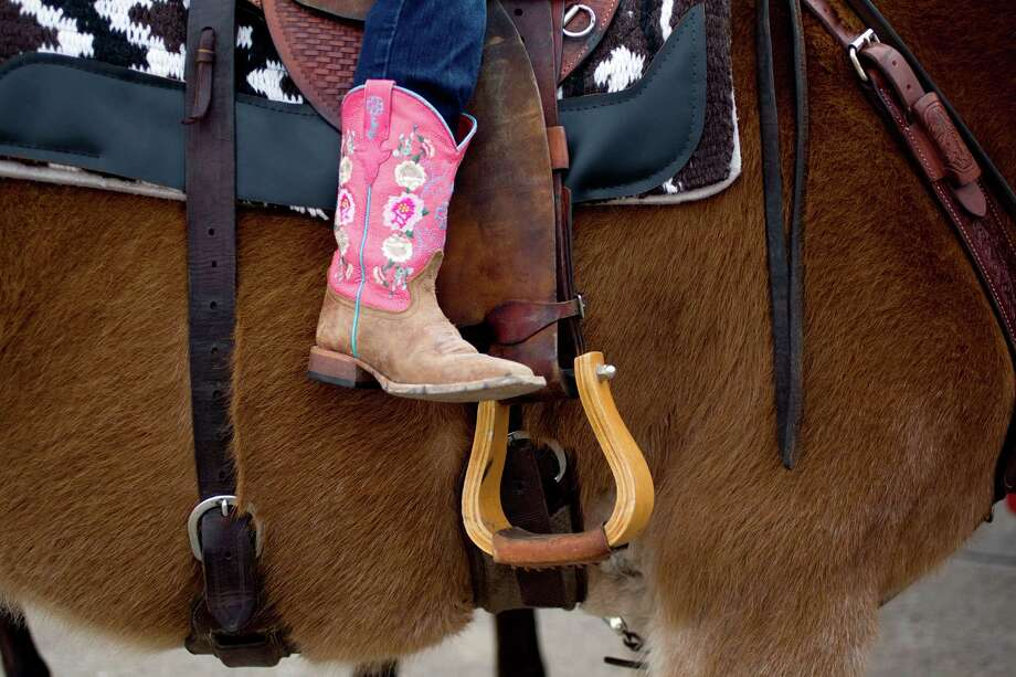 Mikenzy Whitmire, 6, from Cleveland, sits on her mule named Rose as The Spanish Trail Ride group prepared to make their way from a parking lot on Shepherd near 43rd to Memorial Park to kick off the Houston Livestock Show and Rodeo Friday, Feb. 22, 2013, in Houston. Photo: Johnny Hanson, Houston Chronicle / © 2013  Houston Chronicle