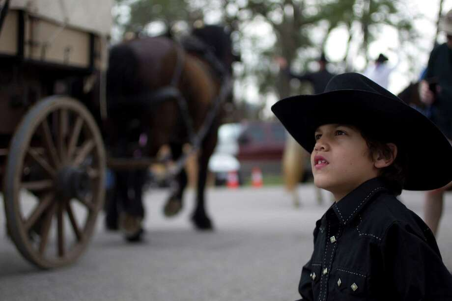 Evan Moak, 7, watched as the Southwestern Trail Ride group rode into Memorial Park to kick off the Houston Livestock Show and Rodeo after their 102 mile ride from Angleton Friday, Feb. 22, 2013, in Houston. Photo: Johnny Hanson, Houston Chronicle / © 2013  Houston Chronicle