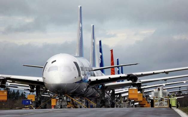 FILE - This Feb. 5, 2013 file photo shows a line of Boeing 787 jets parked nose-to-tail at Paine Field in Everett, Wash. Congressional officials say Boeing is proposing a long-term fix for the 787 Dreamliner's troubled batteries that won't have the planes back in the air until April at the earliest. Boeing officials were presenting their plan Friday to the Federal Aviation Administration. (AP Photo/Elaine Thompson, File) Photo: Elaine Thompson