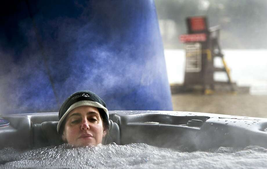 Kai Morimoto keeps warm in a steaming hot tub as she awaits her 16th polar plunge of the day into the icy waters of Liberty Lake, Friday Feb. 22, 2013, in Liberty Lake, Wash.  Morimoto  was one of a dozen people who raised at least $650 in support of Special Olympics of Washington. (AP Photo/The Spokesman-Review, Dan Pelle)  COEUR D'ALENE PRESS OUT Photo: Dan Pelle, Associated Press
