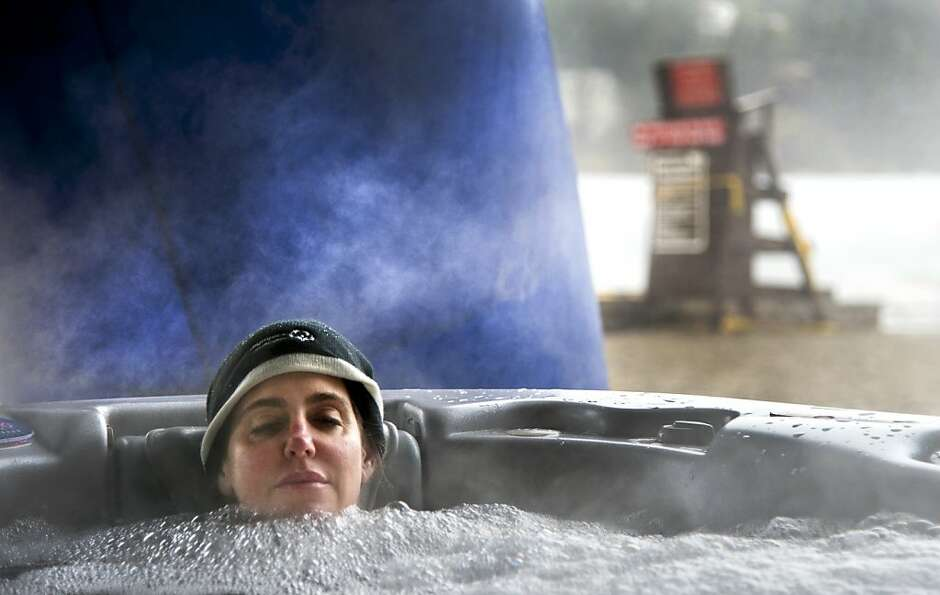 Kai Morimoto keeps warm in a steaming hot tub as she awaits her 16th polar plunge of the day into th