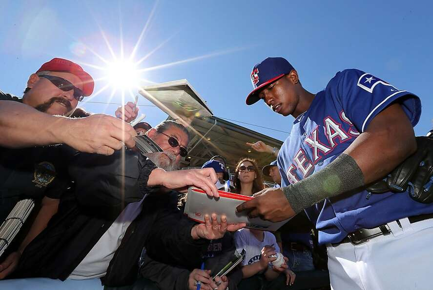 SURPRISE, AZ - FEBRUARY 22:  Jurickson Profar #13 of the Texas Rangers signs autographs for fans bef
