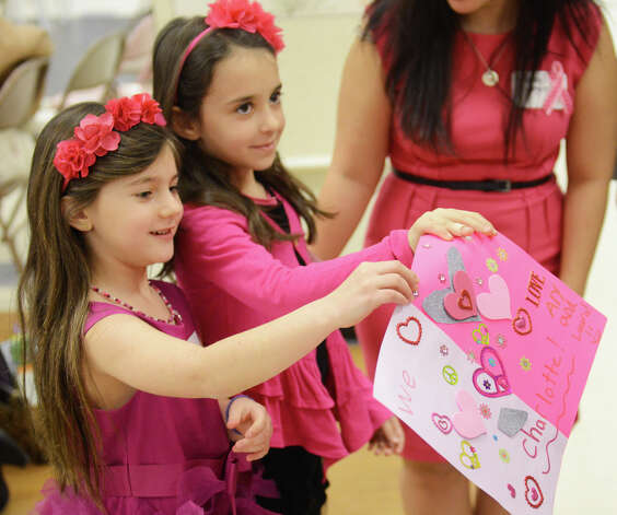 "Aly Oleyar, left, 7, and Laura Crowley, 7, both of Monroe, Conn., present JoAnn Bacon, mother of Charlotte Bacon, who was killed in the Sandy Hook Elementary School shooting, with a ""We love Charlotte"" card before the Newtown Kindness First Annual Charlotte Bacon Act of Kindness Awards at Healing Newtown Arts Space in Newtown, Conn. Friday, Feb. 22, 2013. Photo: Tyler Sizemore / The News-Times"