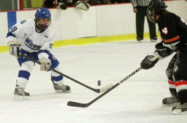 Darien's Robert Juterbock passes the puck during Friday's FCIAC quarterfinal game against Stamford at Terry Connors Rink on February 22, 2013. Photo: Lindsay Perry / Stamford Advocate