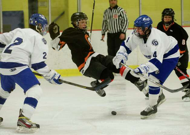 Stamford's Andrew Kydes is airborne as he is surrounded by Darien's Brendan Cassidy, right, and Nicholas Allam, left, during Friday's FCIAC quarterfinal game against Darien at Terry Connors Rink on February 22, 2013. Photo: Lindsay Perry / Stamford Advocate