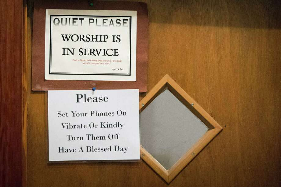 Signs advise worshippers to turn off their cell phones on the door into the sanctuary at Mt. Calvary Missionary Baptist Church on Saturday, Feb. 9, 2013, in Houston. Photo: Smiley N. Pool, Houston Chronicle / © 2013  Houston Chronicle