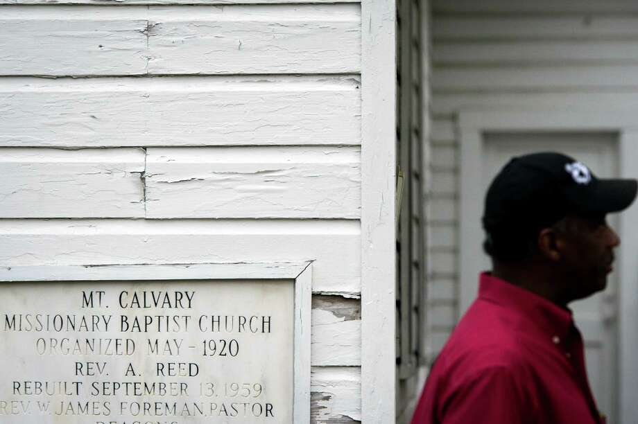 Pastor Maurice A. Johnson stands next to a marker detailing the history of Mt. Calvary Missionary Baptist Church on Saturday, Feb. 9, 2013, in Houston. Photo: Smiley N. Pool, Houston Chronicle / © 2013  Houston Chronicle