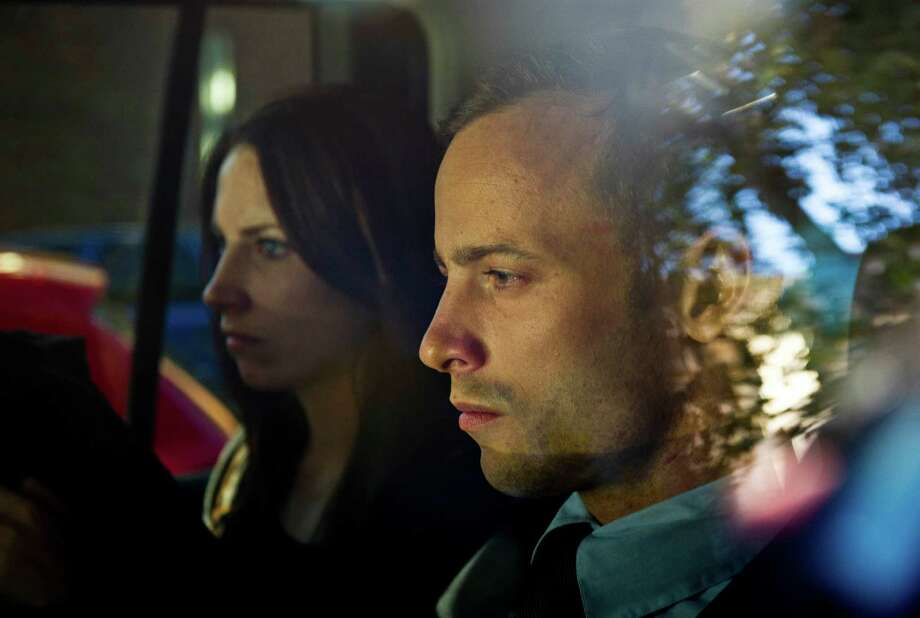 Olympic athlete Oscar Pistorius, right, and his sister Aimee, are driven to a relative's home in Pretoria, South Africa. Pistorius was freed on bail and will return to court June 4 to face charge a charge of murder in the death of Reeva Steenhamp. Photo: Waldo Swiegers, STF / AP