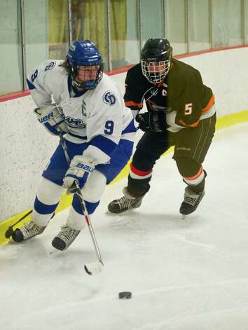 Darien's Dana Wensberg controls the puck as he is guarded by Stamford's Cole Savona during Friday's FCIAC quarterfinal game at Terry Connors Rink on February 22, 2013. Photo: Lindsay Perry / Stamford Advocate