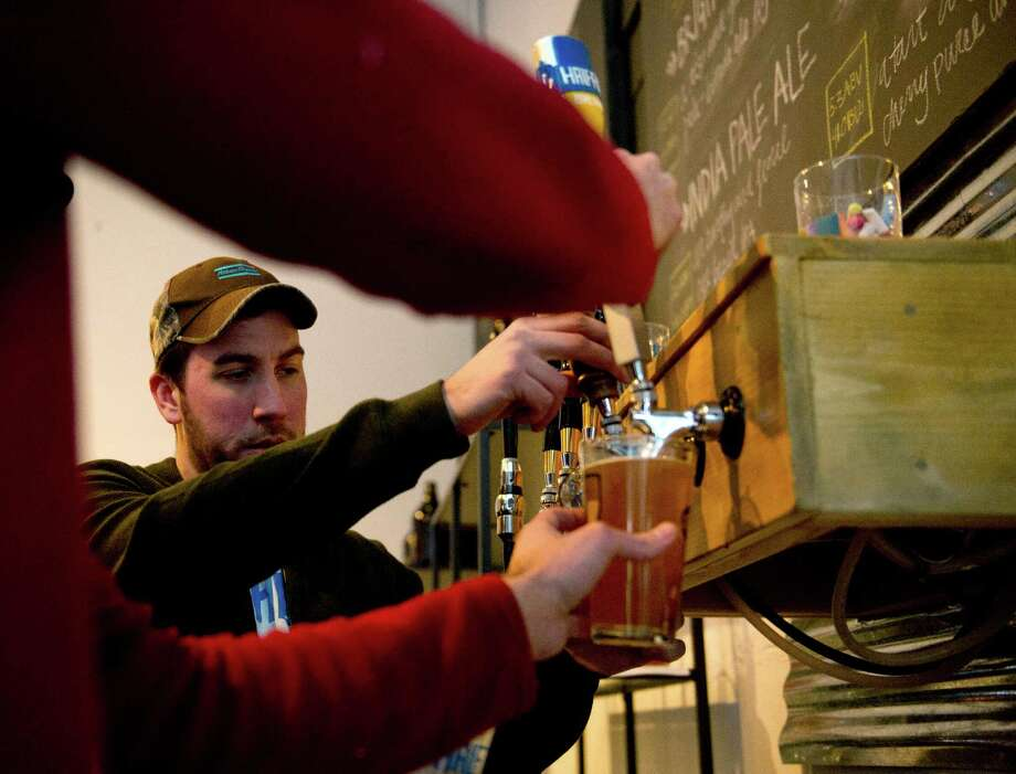 Beer is served as a crowd gathers for drinks and games at Half Full Brewery on Friday, February 22, 2013. Photo: Lindsay Perry / Stamford Advocate