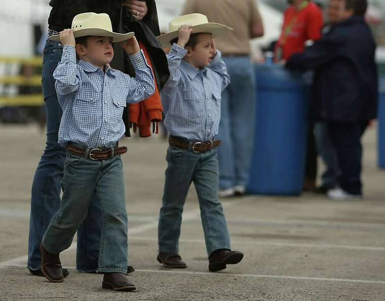 Five-year-old Kyle Prati left, and his twin brother Jack Prati hang on to their hats during the Hous
