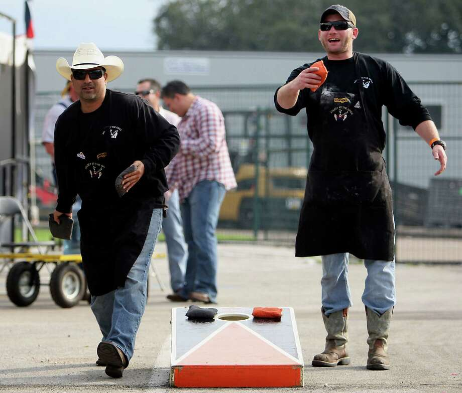 Fred White, left, throws a sand bag while playing a game of corn hole as Chris Jackson right, looks on during the Houston Livestock Show and Rodeo World's Championship Bar-B-Que Contest at Reliant Park Friday, Feb. 22, 2013, in Houston. Photo: James Nielsen, Houston Chronicle / © 2013  Houston Chronicle