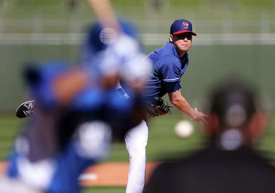 Rangers relief pitcher Coty Woods tries to slow down the Royals during Friday's spring training opener for both teams. The game was tied 5-5 when it was called after nine innings. Photo: Christian Petersen / Getty Images