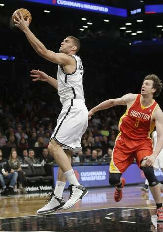 Brook Lopez of the Nets drives past Rockets center Omer Asik.