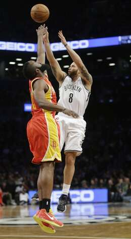 Nets point guard Deron Williams shoots over Rockets shooting guard James Harden.