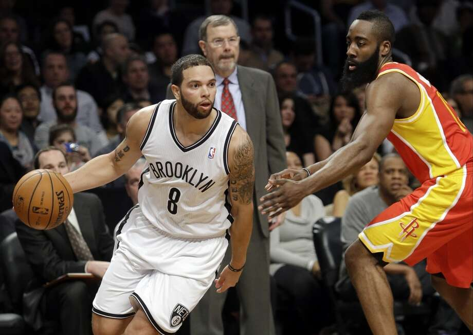 Deron Williams of the Nets drives past Rockets guard James Harden.