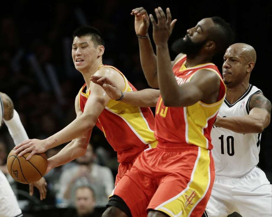 Rockets guards Jeremy Lin and teammate James Harden collide as Keith Bogans of the Nets defends.
